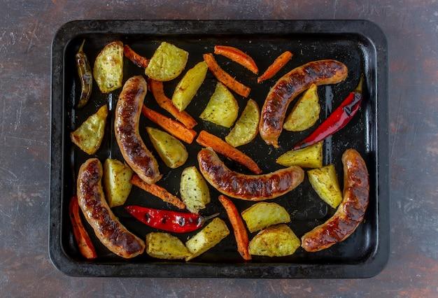 Salsichas grelhadas com batatas, cenouras e pimentões. cozinha alemã.