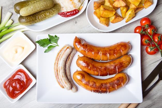 Salsichas grelhadas com batatas, pepinos e chucrute, com dois molhos. close-up, foco seletivo.