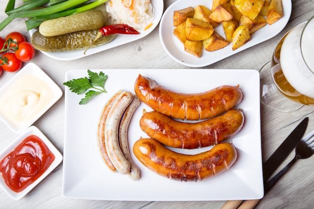 Salsichas grelhadas com batatas, pepinos e chucrute, com dois molhos.