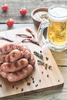Salsichas grelhadas com caneca de cerveja