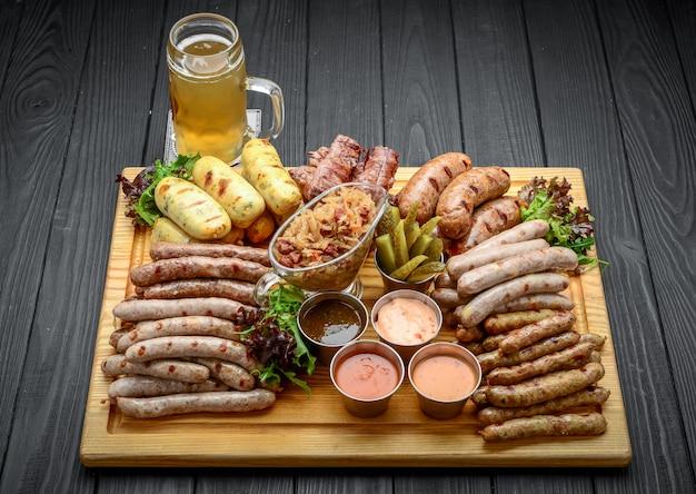 Salsichas grelhadas com copo de cerveja em uma mesa de madeira