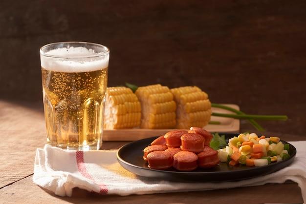 Salsichas grelhadas com copo de cerveja na mesa de madeira com espaço de cópia.