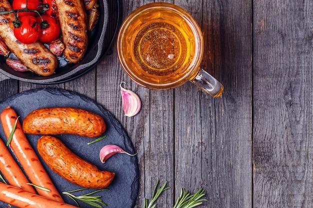 Salsichas grelhadas com copo de cerveja na mesa de madeira. vista superior com espaço de cópia.