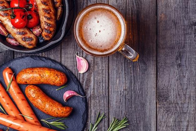 Salsichas grelhadas com copo de cerveja na mesa de madeira