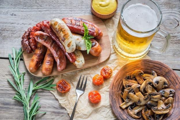 Salsichas grelhadas com copo de cerveja