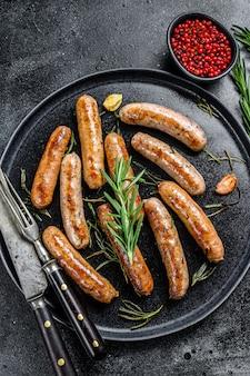 Salsichas grelhadas com ervas de alecrim, carnes bovina e suína. fundo preto. vista do topo.
