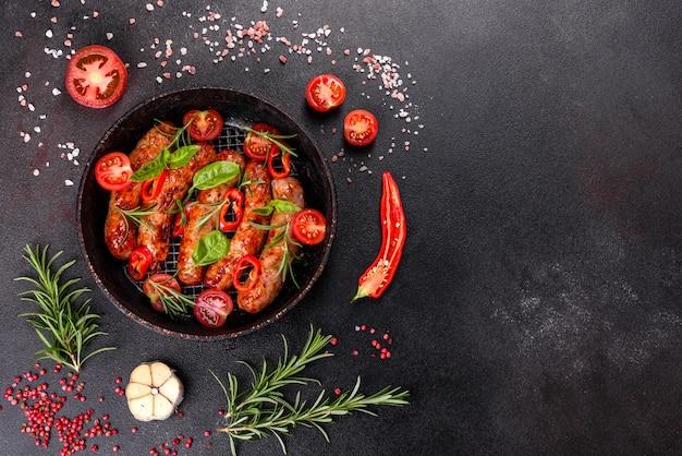 Salsichas grelhadas com legumes e especiarias em fundo preto