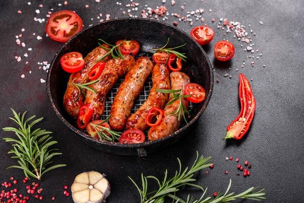 Salsichas grelhadas com legumes e especiarias na mesa preta