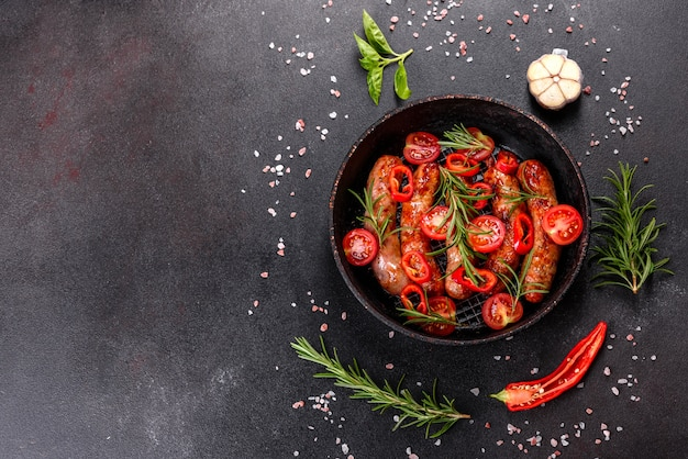 Salsichas grelhadas com legumes e temperos no preto