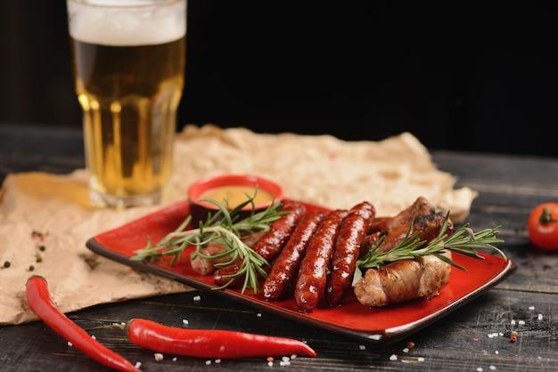 Salsichas grelhadas com molho de alecrim e mostarda. em um prato vermelho em uma mesa de madeira