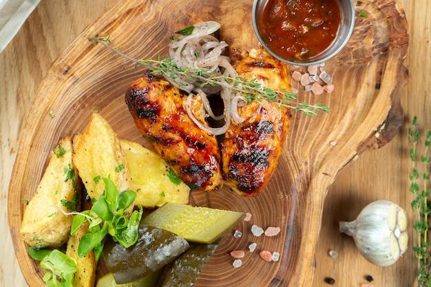 Salsichas grelhadas com molho de mel e cerveja serviram em uma tábua de madeira com ervas, batata frita, pepinos em conserva e couve. cozinha caseira alemã e bávara. foco seletivo