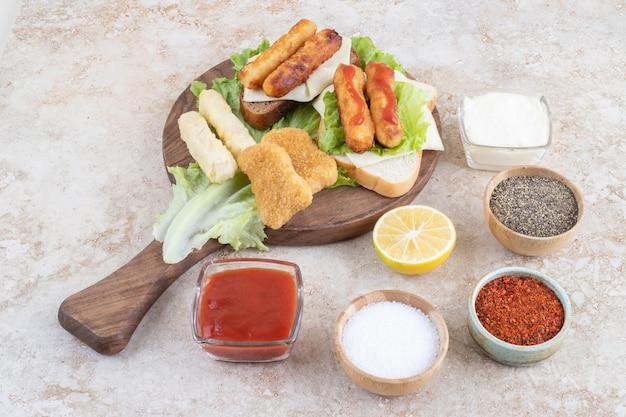 Salsichas grelhadas com nuggets de frango em um pedaço de alface em uma placa de madeira com molhos à parte.