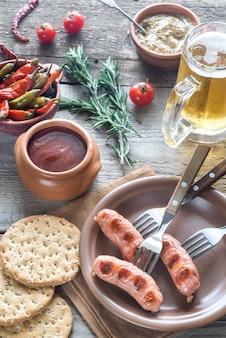 Salsichas grelhadas com petiscos e caneca de cerveja