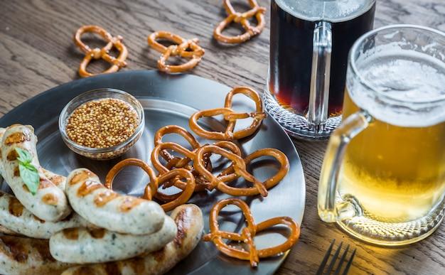 Salsichas grelhadas com pretzels e canecas de cerveja