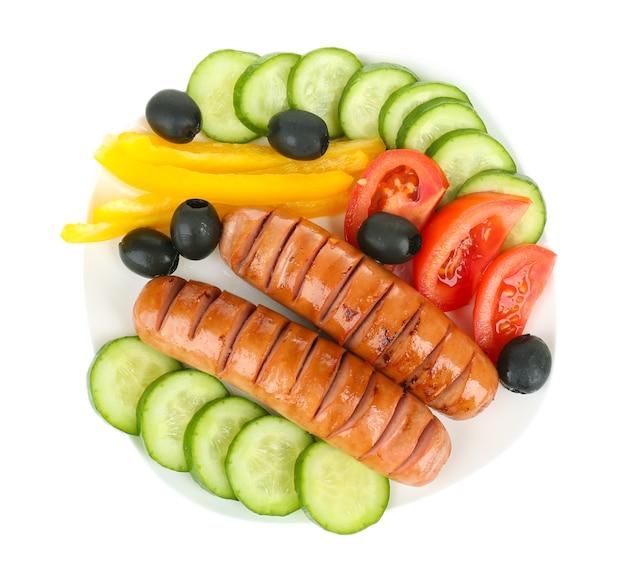 Salsichas grelhadas com vegetais isolados no branco