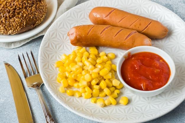 Salsichas grelhadas, conservas de milho e molho de tomate em um prato