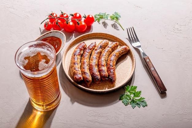 Salsichas grelhadas de carne bovina e suína com molho barbecue em um prato e um copo de cerveja na mesa, foto com tendência de forte luz do sol e sombras.