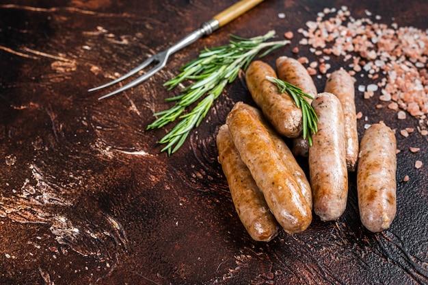 Salsichas grelhadas de carne de porco e carne bovina na mesa da cozinha. fundo escuro. vista do topo. copie o espaço.