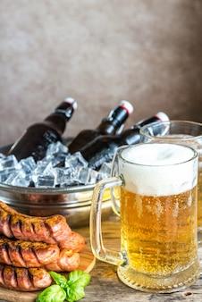 Salsichas grelhadas e canecas de cerveja