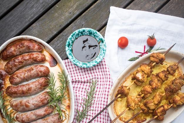 Salsichas grelhadas e espetinhos na mesa