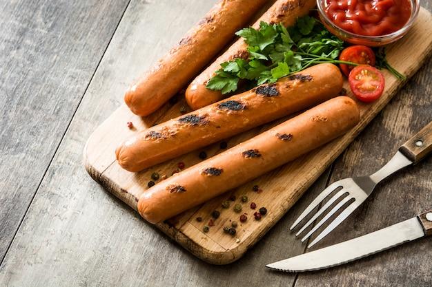 Salsichas grelhadas e molho de ketchup na mesa de madeira