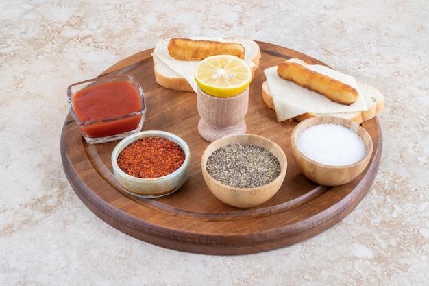 Salsichas grelhadas e nuggets de frango em torrada sanduíche servida com molhos.