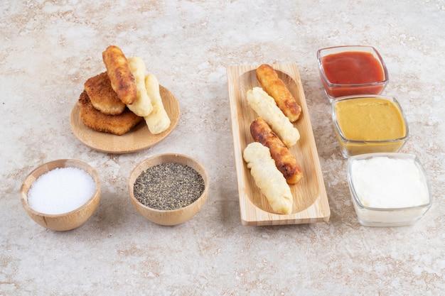 Salsichas grelhadas e palitos de queijo servidos com molhos.