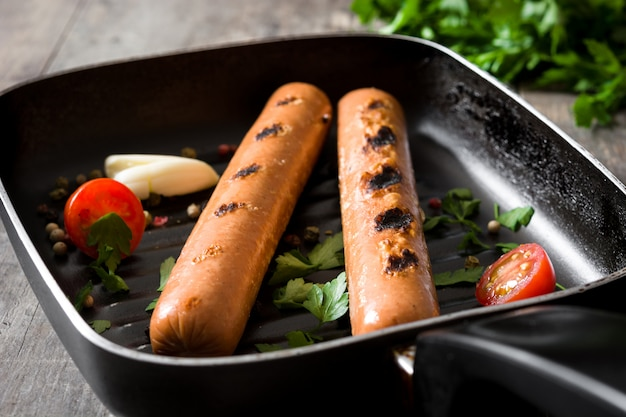 Salsichas grelhadas em frigideira de ferro na mesa de madeira