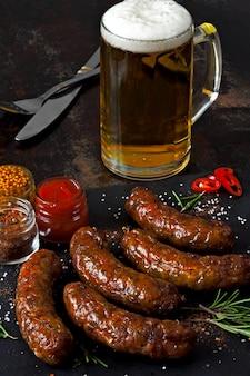 Salsichas grelhadas em uma placa de pedra escura com um copo de cerveja.