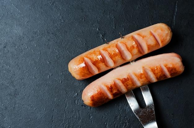 Salsichas grelhadas fritas em um garfo de metal. dieta não saudável.