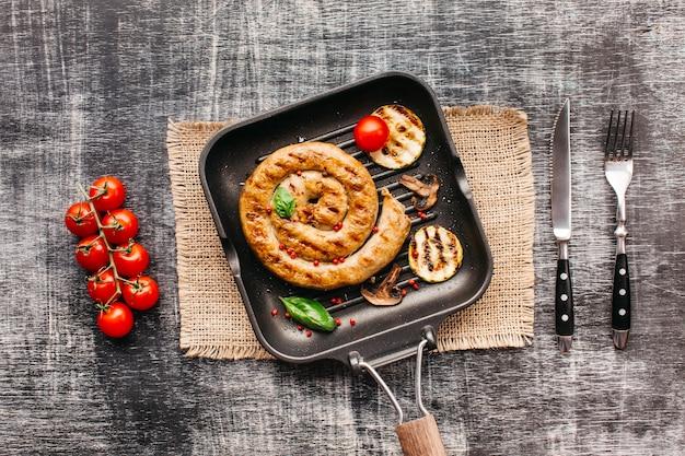 Salsichas grelhadas gostosas espirais em panela com vegetais no plano de fundo texturizado