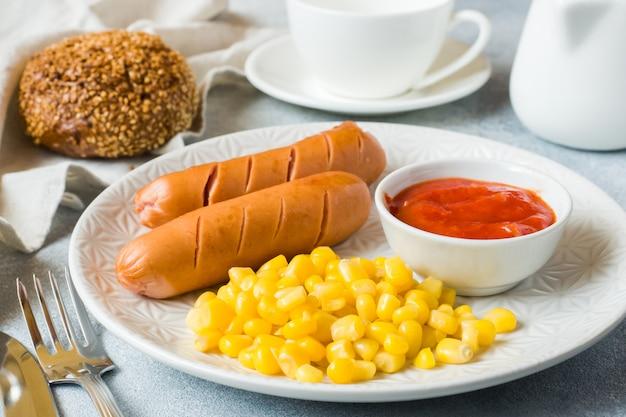 Salsichas grelhadas, milho enlatado e molho de tomate em um prato