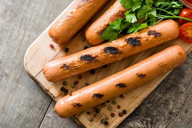 Salsichas grelhadas na mesa de madeira