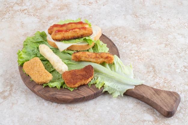 Salsichas grelhadas, palitos de queijo e nugges de frango em uma folha de alface.