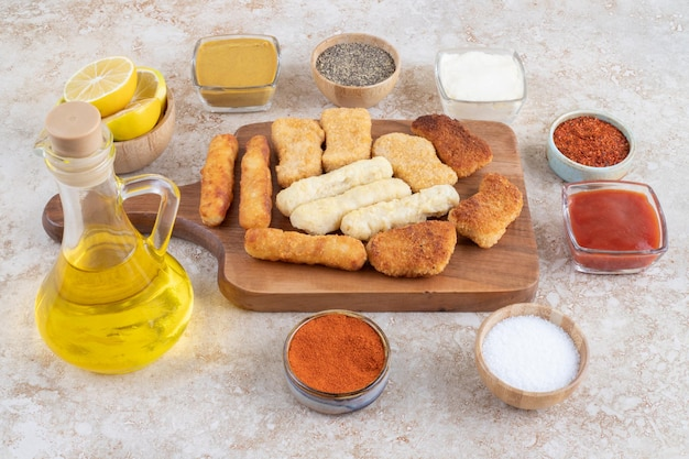 Salsichas grelhadas, palitos de queijo e nuggets de frango com molhos em travessa de madeira.