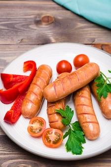 Salsichas grelhadas, tomates frescos, pimentos e salsa em uma placa sobre uma mesa de madeira
