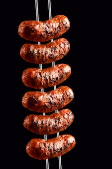 Salsichas na churrasqueira cuspindo no espaço negro
