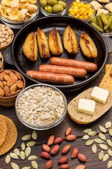 Salsichas na frigideira. queijo, vegetais, biscoitos, cereais: ingredientes para o café da manhã continental.