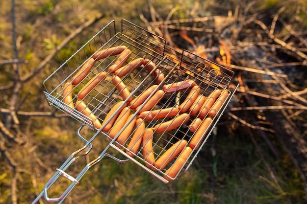 Salsichas na grelha na fogueira. um piquenique na natureza ao pôr do sol. gosto do verão