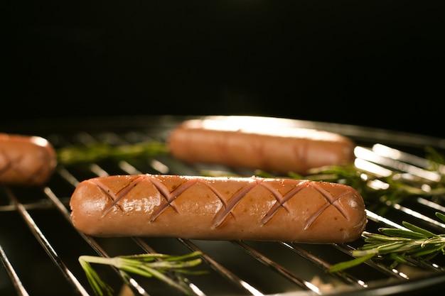 Salsichas na grelha quente com fumaça