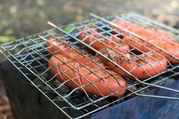 Salsichas na grelha sobre o fogo.