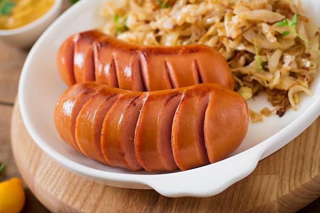 Salsichas na panela de grelhar na mesa de madeira