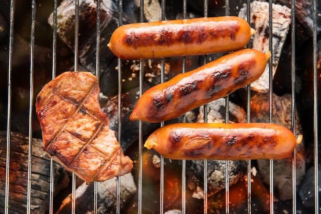 Salsichas para churrasco e carne na grelha.