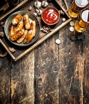 Salsichas quentes com cerveja gelada. sobre um fundo de madeira.