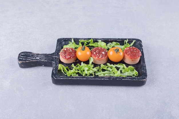 Salsichas saborosas fatiadas com ketchup e tomate no quadro negro.