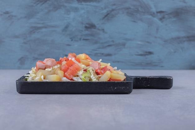 Salsichas saborosas fatiadas com salada fresca no quadro negro.