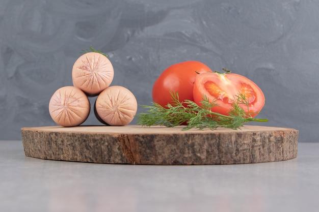 Salsichas saborosas fervidas e tomates na peça de madeira.