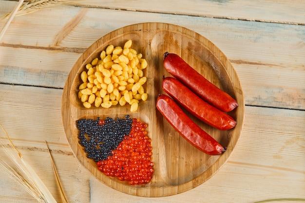 Salsichas, sementes de milho cozidas e caviar em uma placa de madeira.