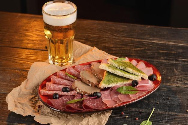 Salsichas sortidas, jamon e presunto com fatias de pão frito num prato vermelho. em uma mesa de madeira