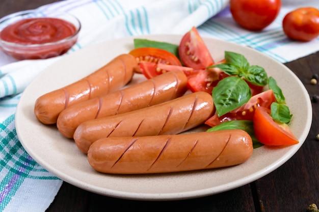 Salsichas suculentas com tomate e folhas de manjericão no prato na mesa de madeira escura